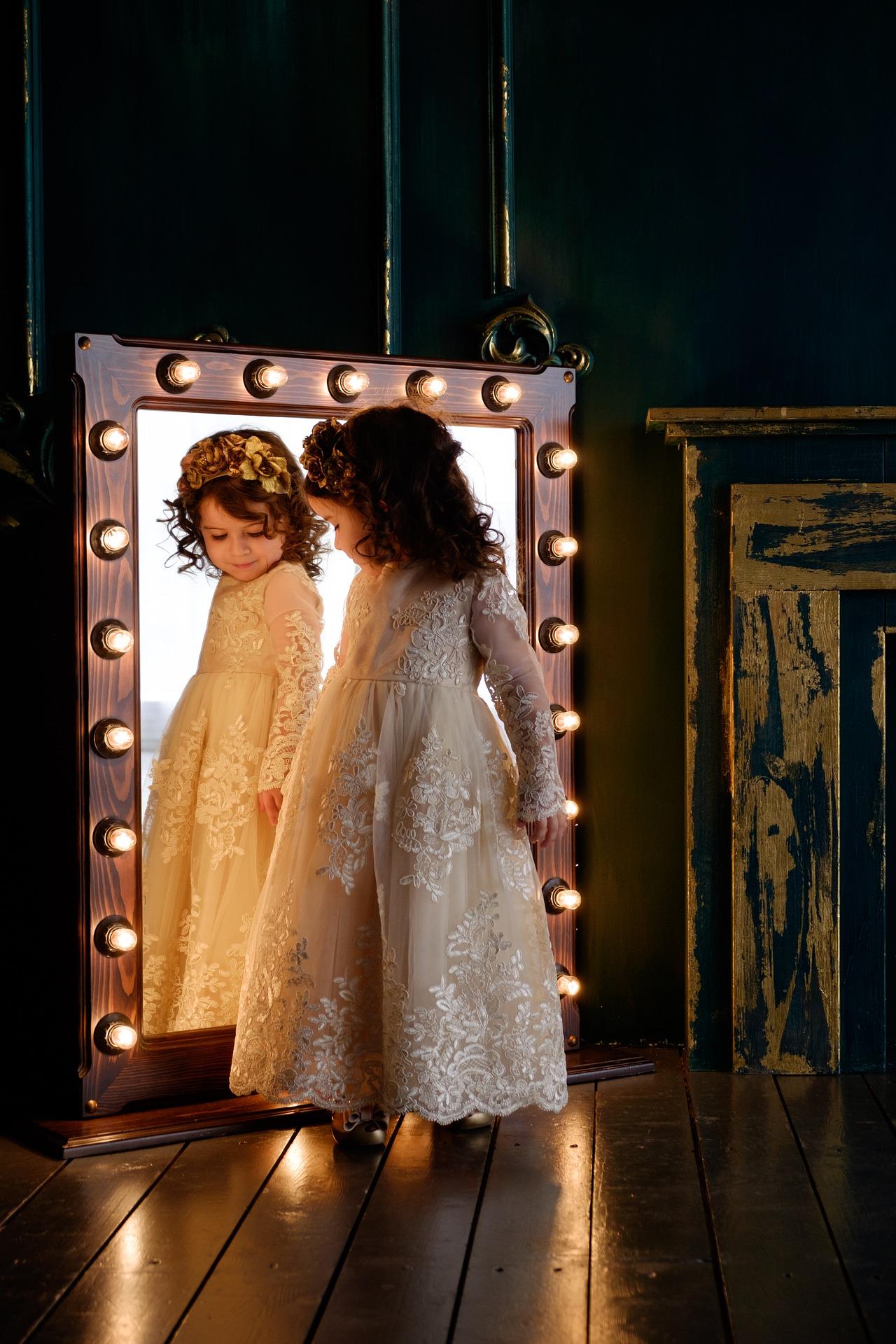Une petite fille se regarde dans un miroir